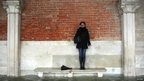 A woman stands on a bench above a flooded street in Venice on 11 November 2012. 