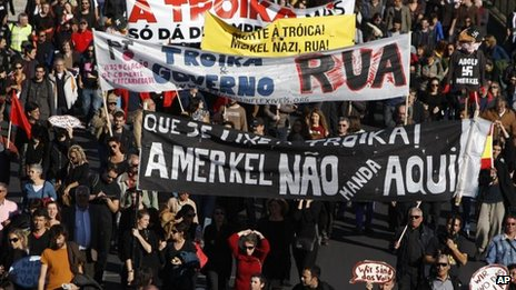 Demonstrators hold banners protesting the visit to Portugal of German Chancellor Angela Merkel, Lisbon, 12 Nov