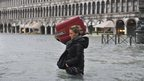 A tourist crosses a flooded St Mark's Square in Venice on 11 November 2012