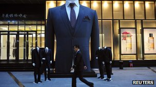 A man walks past a big suit at a shopping mall in Shenyang, Liaoning province 28 October 2012