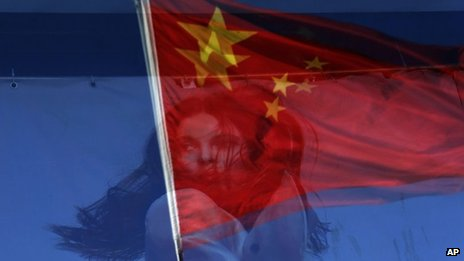 The Chinese flag is reflected on a fashion poster at a shopping mall in Beijing, China, 12 November 2012