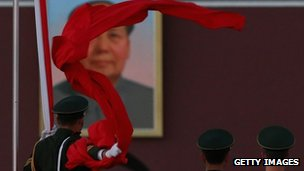 A paramilitary police in front of a giant portrait of the late chairman Mao Zedong in Beijing, 13 November 2012