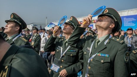 Officers of China&#039;s People Liberation Army (PLA) watch planes performing during the 9th China International Aviation and Aerospace Exhibition in Zhuhai, 13 November 2012
