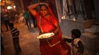 An Indian woman holds a tray filled with earthen lamps during Diwali celebrations in New Delhi, India, Tuesday, Nov. 13, 2012.