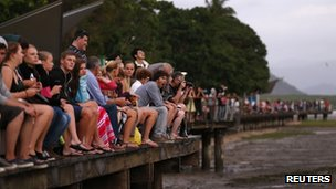 Tourists look at a cloudy sky as a full solar eclipse begins in the northern Australian city of Cairns November 14, 2012.