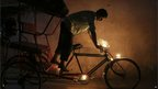An Indian man stands on his bicycle rickshaw after placing candles on it for good luck and fortune during the festival of Diwali in New Delhi, India, Tuesday, Nov. 13, 2012.