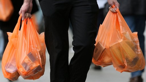 Shopper carries Sainsburys plastic bags full of shopping