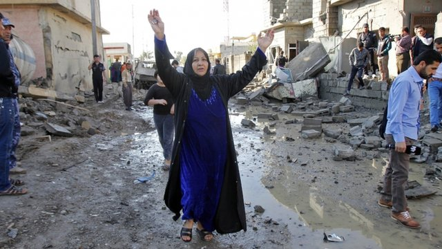A woman running down street in Kirkuk after blast