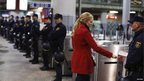A woman passes through a ticket barrier guarded by dozens of police officers at Atocha railway station in Madrid, Spain.