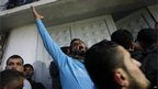 A Palestinian man raises his arm in anger at the hospital in Gaza where Jabari's body was brought