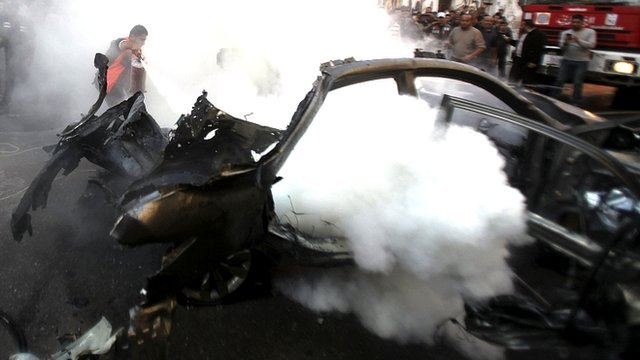 A Palestinian helps extinguish the fire after an Israeli air strike on a car in Gaza City November