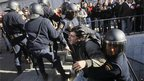 A riot policeman in Madrid arrests a protester.