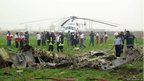 Iranian rescuers inspect the debris of a helicopter that crashed