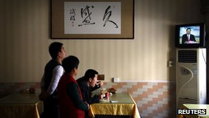 """A customer eats his lunch next to restaurant workers and underneath a painting of Chinese characters that reads """"Long-lasting Prosperity"""""""