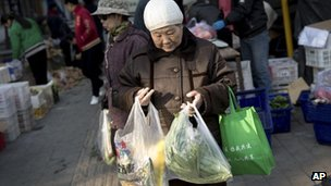 Chinese residents buy daily groceries from a mobile vegetable seller near a residential area in Beijing Thursday, Nov. 15