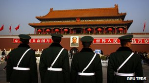 Paramilitary policemen standing guard in front of the giant portrait of former Chinese Chairman Mao Zedong at Beijing's Tiananmen Square, 15 November 2012