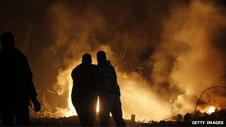 Palestinians try to extinguish fire following an Israeli air strike on November 14