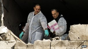 Israeli forensic experts inspect a damaged house hit by a rocket fired by Palestinian militants from the Gaza Strip in the southern Israeli city of Kiryat Malachi (15 Nov 2012)