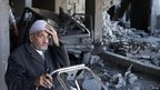 A Palestinian man sits inside a damaged house after Israeli air strikes in Gaza City.
