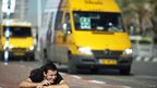 An Israeli man takes cover as a siren sounds warning of incoming rockets in Ashdod November 15, 2012.