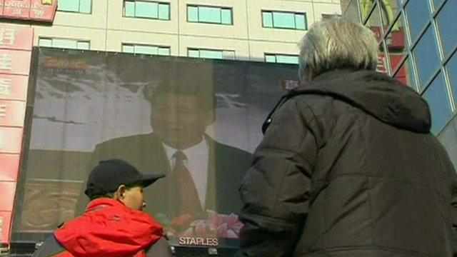Beijing residents looking at a giant TV screen broadcast of the announcement