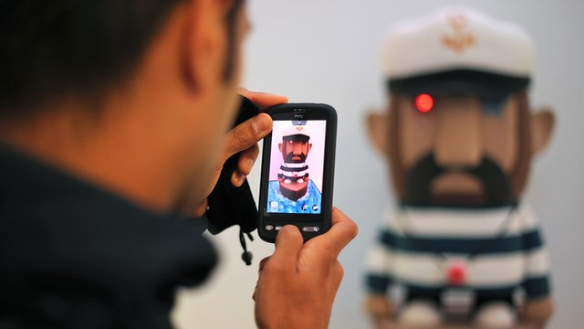 A visitor uses his mobile phone to photograph a work of art entitled 'Captain Fairtrade' made from sugar coated sponge, during a exhibition of edible art in London
