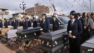 The coffins of dead farm workers are lined up during a funeral ceremony in Santa Rosa de Osos