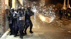 Spanish riot police officers protect themselves from a projectile in Madrid