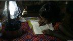 A girl reads by lantern light