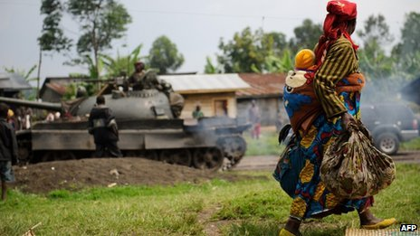 A displaced  woman carrying her child walks past an army tank in eastern Democratic Republic of Congo (26 July 2012)