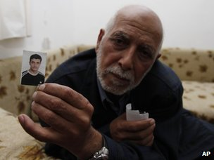 The father of Qais Omari holds up a photo of his son (15 November 2012)
