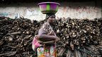 A woman carrying her baby walks past stacked wood near the final campaign rally for Sierra Leone opposition presidential candidate in Freetown