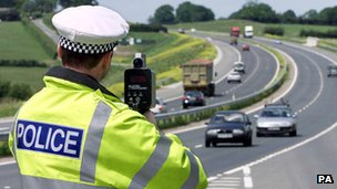 A policeman points a speed gun at cars on a motorway