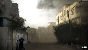 A Palestinian woman and her child run for cover after an Israeli air strike hit the northern Gaza City (16 Nov 2012)