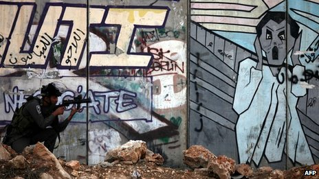 Israeli soldier in front of graffiti