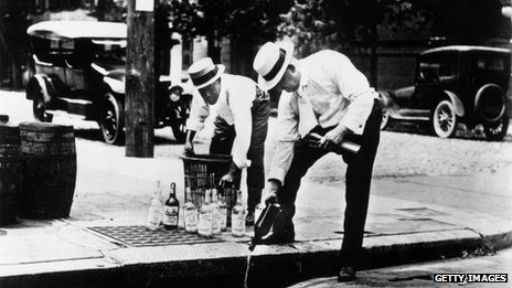 Men pour liquor down a drain in 1920