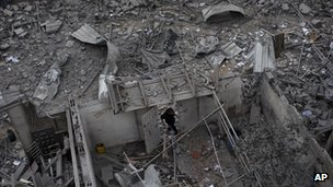 A Palestinian man walks among debris after an Israeli airstrike at Hamas Prime Minister Ismail Haniyeh&#039;s office in Gaza City, Saturday, Nov. 17, 2012.