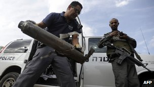 An Israeli bomb disposal expert (C) removes the remains of a rocket fired in Sde Uziyahu November 17, 2012.