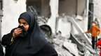 Palestinian woman outside her damaged house in Jabaliya, northern Gaza (17 Nov)