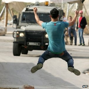 A Palestinian youth gestures at Israeli soldiers at the Jalama checkpoint, West Bank. Photo: 17 November 2012 