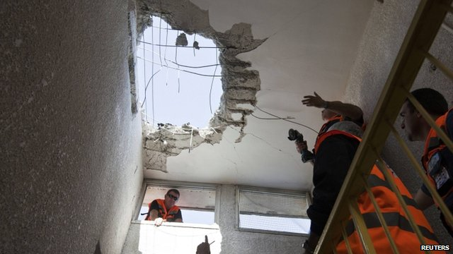 Israeli rescue workers look at the roof of a building damaged by a rocket in the coastal city of Ashkelon November 18, 2012.