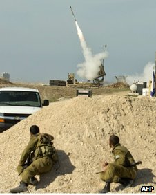 Israeli soldiers take cover as an Israeli missile is launched from the Iron Dome defence missile system  in the southern Israeli city of Ashdod, November 18
