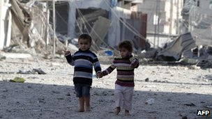 Palestinians children walk past destroyed buildings in Rafah on November 18, 2012