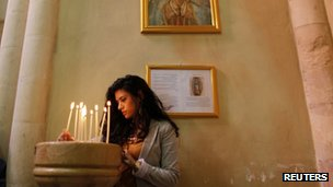 Palestinian lights a candle in a church near Bethlehem for Gaza November 18, 2012