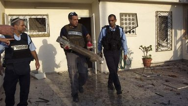 Israeli police carry the remains of a rocket in the southern town of Ofakim, 18 Nov