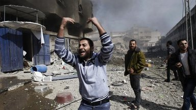 Palestinians call for help as they stand next to a damaged building after an Israeli air strike in Gaza City, 18 Nov