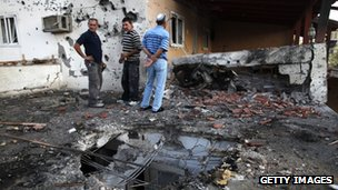 Israeli civilians inspect the damage to a house in Ofakim