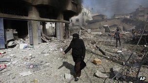 A Palestinian woman walks past damage in Gaza City (18 Nov 2012)