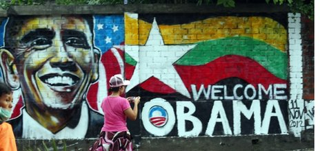 A woman takes a photo of a wall painting created by Burmese graffiti artists to welcome President Barack Obama in Rangoon