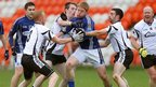 St Gall's player Terry O'Neill finds himself closed down by Kilcoo opponents Niall McEvoy, Paul Devlin and Donal Kane